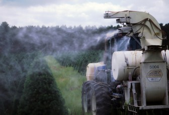 Machinery sprays pesticide on rows of Christmas trees at a tree farm near Wautoma, Wis.