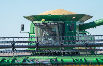 A combine with a full hopper of soybeans heads to a waiting truck at a harvest just north of Mansfield, Ill., on Wednesday, Oct. 9, 2013.