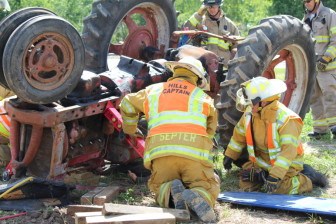 A dummy placed beneath a rolled over tractor gives Eastern Iowa firefighters a chance to practice their response in situations involving a farmer. This photo is from Tractor Rollover Extrication Training put on by the Rural Health and Safety Clinic of Greater Johnson County in Iowa on Aug. 3 at the Johnson County Extension Building in Iowa City, Iowa.