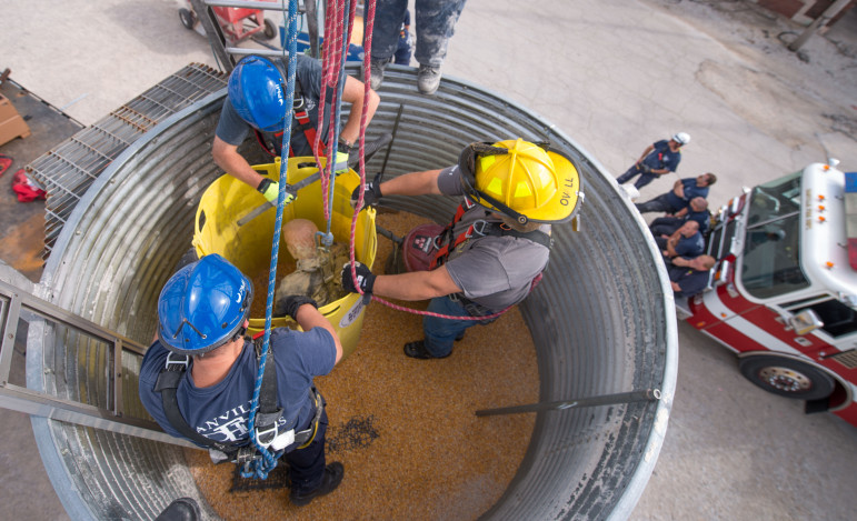 Firefighters practice placing a rescue tube during grain bin rescue training at the Danville Bunge facility on Tuesday, Sept. 17, 2013. photo by Don McMasters/for The Midwest Center for Investigative Reporting