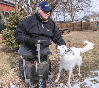 Chip Petrea greets his dog Laddie in his backyard at home in Urbana, Ill.