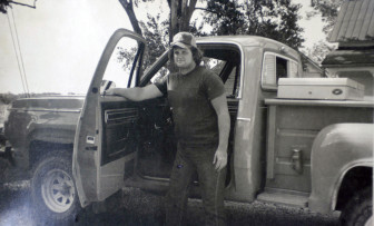 A young Chip Petrea stands next to an old truck parked outside.