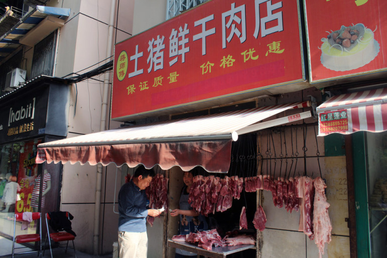 A person stands near a meat store at a market in the city of Chengdu in southwest China. In 2013, China accounted for 16 percent, or $14.4 million, of Tyson's international chicken sales.