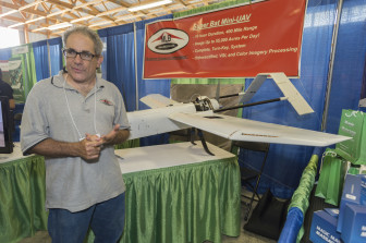 Stephen Morris, president of MLB Company, stands next to the Super Bat UAS at the 2014 Precision Aerial Ag Show in Decatur, Ill. The Super Bat UAS can reach altitudes of 15,000 feet and survey 55,000 acres of crops in one day.
