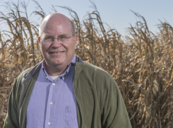 University of Illinois at Urbana-Champaign agricultural economist Gary Schnitkey stands in front of corn at a research plot on Oct. 17, 2014.