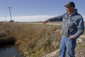 Lin Warfel points to a drainage area on his property on Nov. 5, 2014.