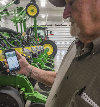 Apgar Farms representative Tom Austin uses a Climate Corporation app on a mobile phone on June 10, 2015.