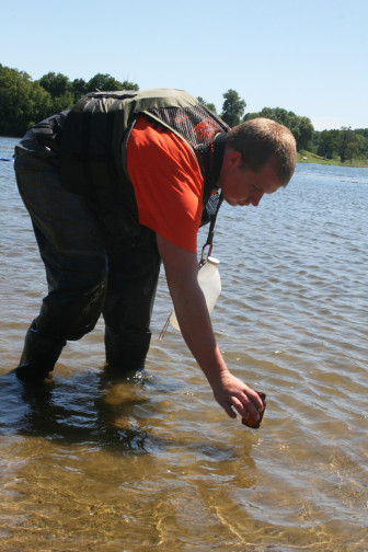 Connor Nicholas, 22, gathers a sample from Prairie Rose Lake on July 30, 2015 as part of the Iowa DNR beach monitoring program.