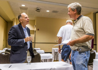 Lawyer and former U.S. representative Bill Enyart talks with farmer Dennis Riggs at the Hilton Garden Inn in Champaign, Ill., on Sept. 1, 2015.
