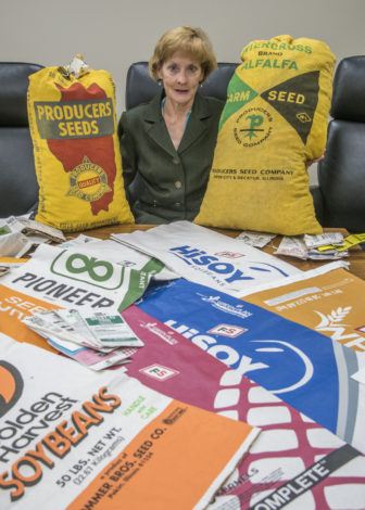 Tamara Nelsen at Illinois Farm Bureau in Bloomington with a variety of seed bags from the past. Wednesday, Oct. 5, 2016.