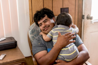 Agustin Chavarria, 41, and his 11 month old baby, Jose, at their temporary home on an orchard just outside of Lexington, Missouri, on June 22, 2016.
