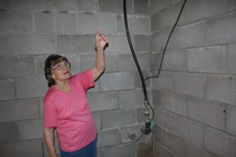 Joan Michels, of Earling, Iowa, points to the water lines coming in her house from the well outside on Aug. 19, 2016.