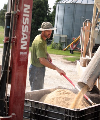 Earl Canfiled mixes ground feed.