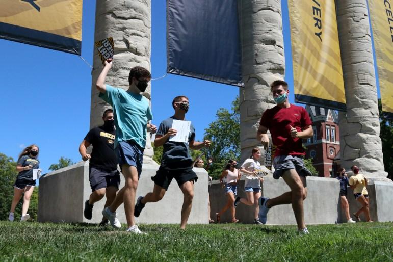 A group of incoming freshman run through the Columns on MU's campus, Aug. 19, 2020.